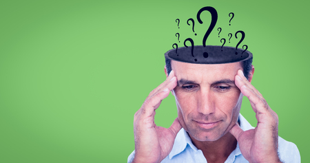Handsome man thinking with hand on forehead against green background Stock Photo