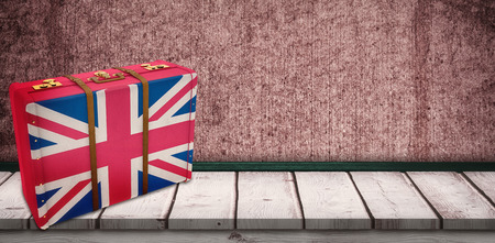 great britain flag: Great Britain flag suitcase against wooden board