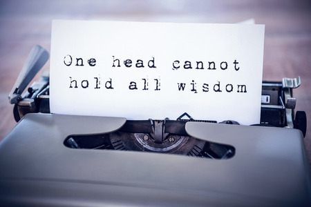 all in one: The sentence one head cannot hold all wisdom against white background against a paper in a printer