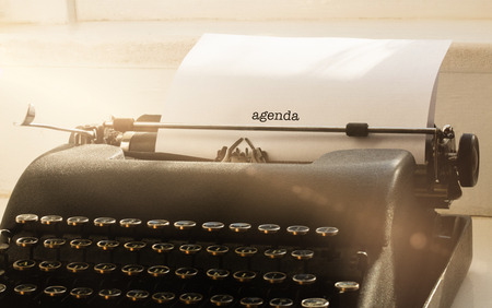 one room school house: The word agenda against typewriter on a table