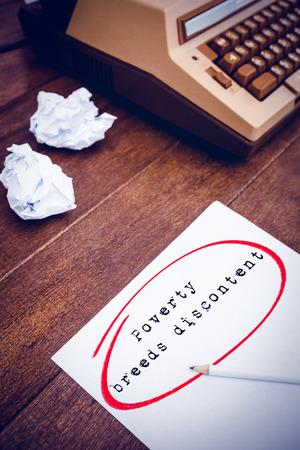 frase: La frase la pobreza engendra descontento contra el fondo blanco en contra de una antigua máquina de escribir y papel