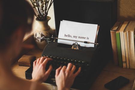 hello my name is: The word hello, my name is against young woman using typewriter Stock Photo