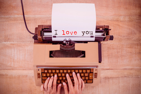 The sentence I love you against white background against above view of old typewriter