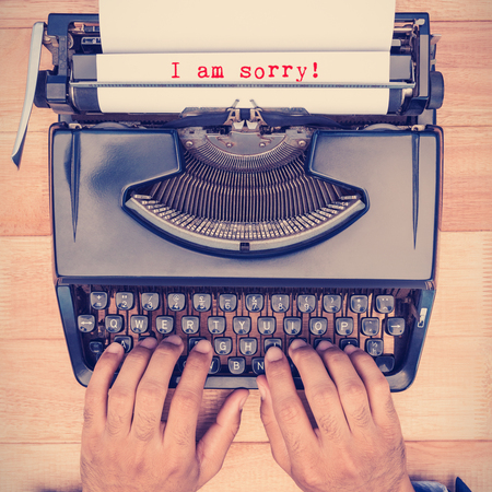 i am sorry: The sentence I am sorry against white background against businessman typing on typewriter