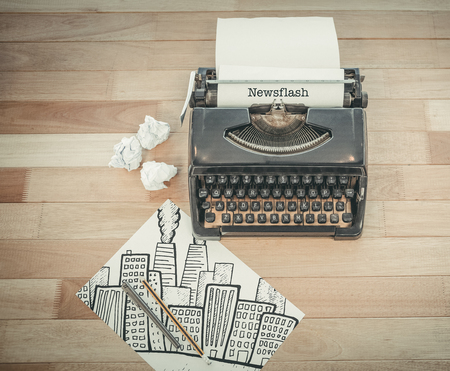 newsflash: The word newsflash and cityscape with brainstorm doodle against typewriter and paper on table in office