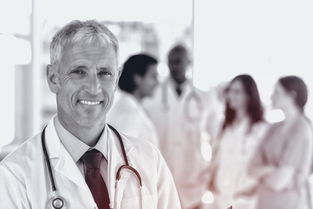 doctors smiling: Smiling doctor waiting for his team while standing upright Stock Photo