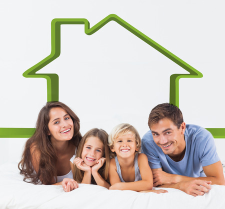 house outline: Happy family lying on a bed against house outline