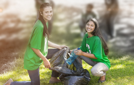 Team of young volunteers picking up litter in the park Фото со стока