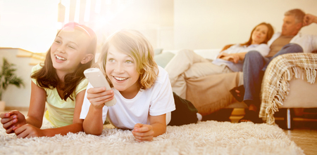 Siblings lying on the floor watching tv together Stock Photo - 56319210