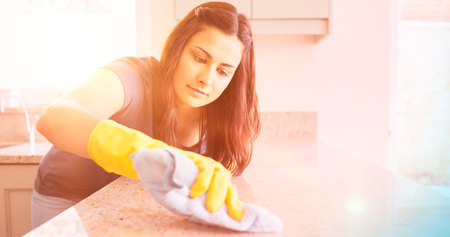 scrubbing: Concentrated woman scrubbing the bar in kitchen Stock Photo
