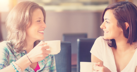 Two smiling students having a cup of coffee in college canteen Stock Photo