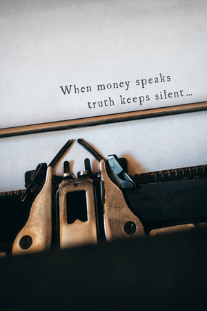 speaks: When money speaks truth keeps silent message on a white background  against close-up of typewriter Stock Photo