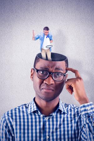 ropa casual: El hombre en la ropa ocasional que habla en el meg�fono contra la pared gris