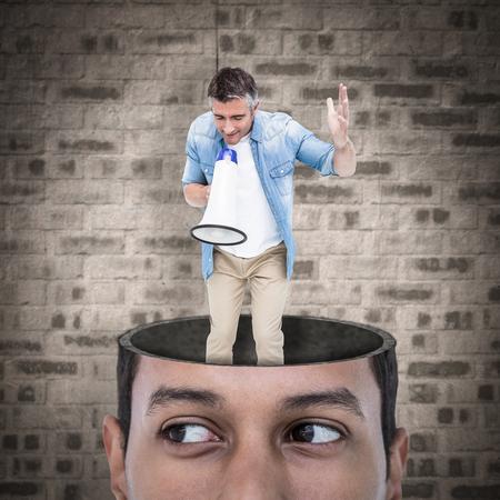 ropa casual: El hombre en la ropa ocasional que habla en el meg�fono contra la pared de piedra