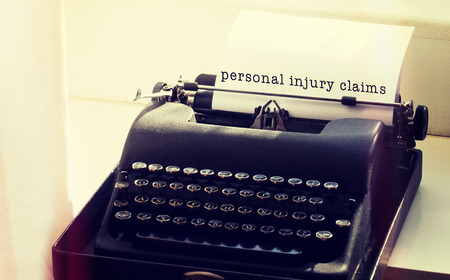 personal injury: Personal injury claims message on a white background against typewriter on a table