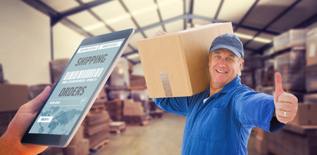 boiler suit: Man using tablet pc against forklift in a large warehouse Stock Photo