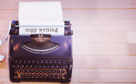 copy writing: Copy writing message on a white background against typewriter with paper on table in office Stock Photo