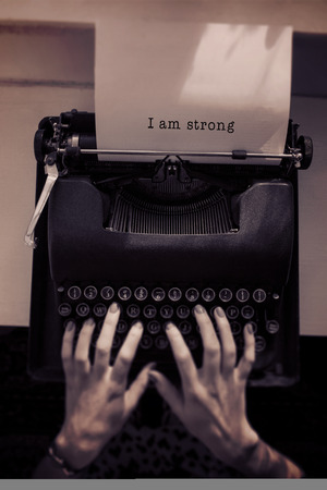 strong message: I am strong message on a white background  against womans hand typing on typewriter