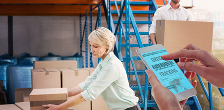 mature adult: Cropped hand using smartphone against warehouse managers loading a trolley