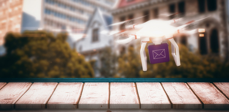 dormer: Digital image of a drone holding a cube against low angle view of city buildings on sunny day Stock Photo
