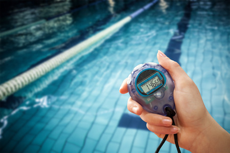 lane marker: Close up of a hand holding a timer on a white background against water moving in the swimming pool
