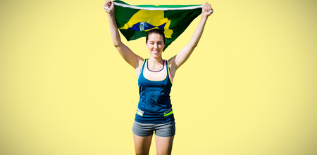 sportswoman: Front view of sportswoman raising Brazilian flag  against yellow background