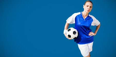 royal blue: Portrait of woman football player is posing  against royal blue Stock Photo