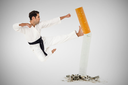 punch press: Fighter performing karate stance against image of pressed cigarette on a white background