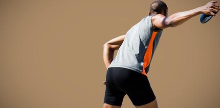 lanzamiento de disco: Vista trasera del deportista practicando el lanzamiento de disco contra el fondo marrón