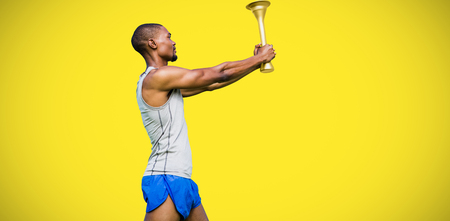 profile view: Profile view of sportsman holding a cup  against yellow background Stock Photo