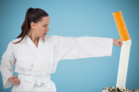 punch press: Fighter performing karate stance against blue background Stock Photo