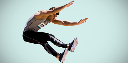 sportsman: Portrait of sportsman jumping  against blue background