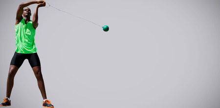 hammer throw: Front view of sportsman practising hammer throw  against light grey