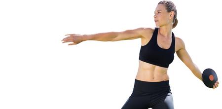 lanzamiento de disco: Concentrated sportswoman practising discus throw