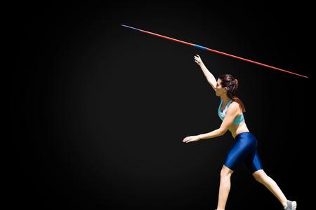lanzamiento de jabalina: Profile view of sportswoman is practising javelin throw