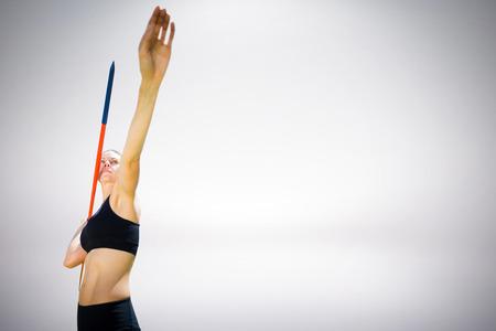 lanzamiento de jabalina: Mujer deportiva que prepara su lanzamiento de jabalina contra el fondo gris