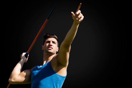 lanzamiento de jabalina: Low angle view of sportsman practising javelin throw