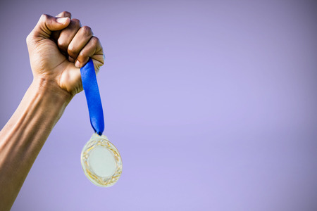 silver medal: Hand holding a silver medal on white background against purple background