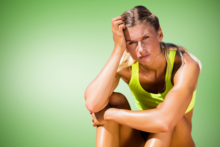 desolaci�n: Sporty woman sitting down and feeling disappointed  against green vignette Foto de archivo