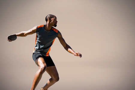 lanzamiento de disco: Hombre atleta lanzando un disco contra el fondo de color beige