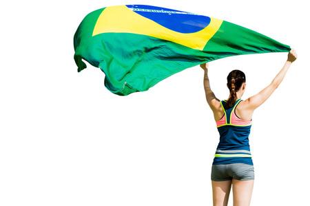 raise the white flag: Rear view of sportswoman raising a brazilian flag Stock Photo