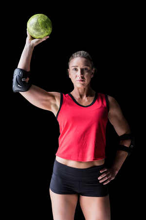 elbow pad: Female athlete with elbow pad holding handball on black background