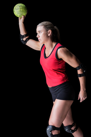 elbow pad: Female athlete with elbow pad throwing handball on black background