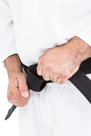 tightening: Fighter tightening karate belt on white background