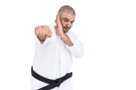 karateka: Portrait of fighter performing karate stance on white background