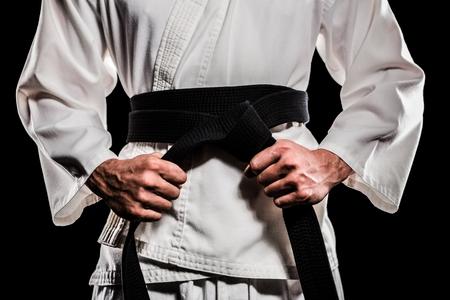 tightening: Fighter tightening karate belt on black background Stock Photo