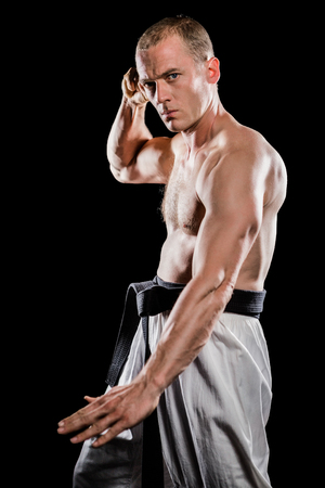 punched out: Portrait of fighter performing karate stance on black background