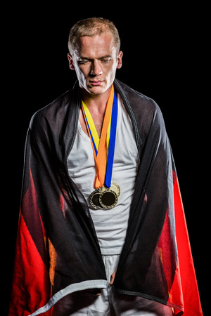 german flag: Athlete posing with german flag wrapped around his body on black background