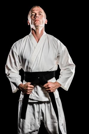 tightening: Portrait of fighter tightening karate belt on black background
