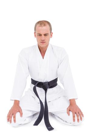 karateka: Front view of karate fighter meditating on white background